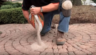 Professional paving company pours new paver sand between cracks of stones.